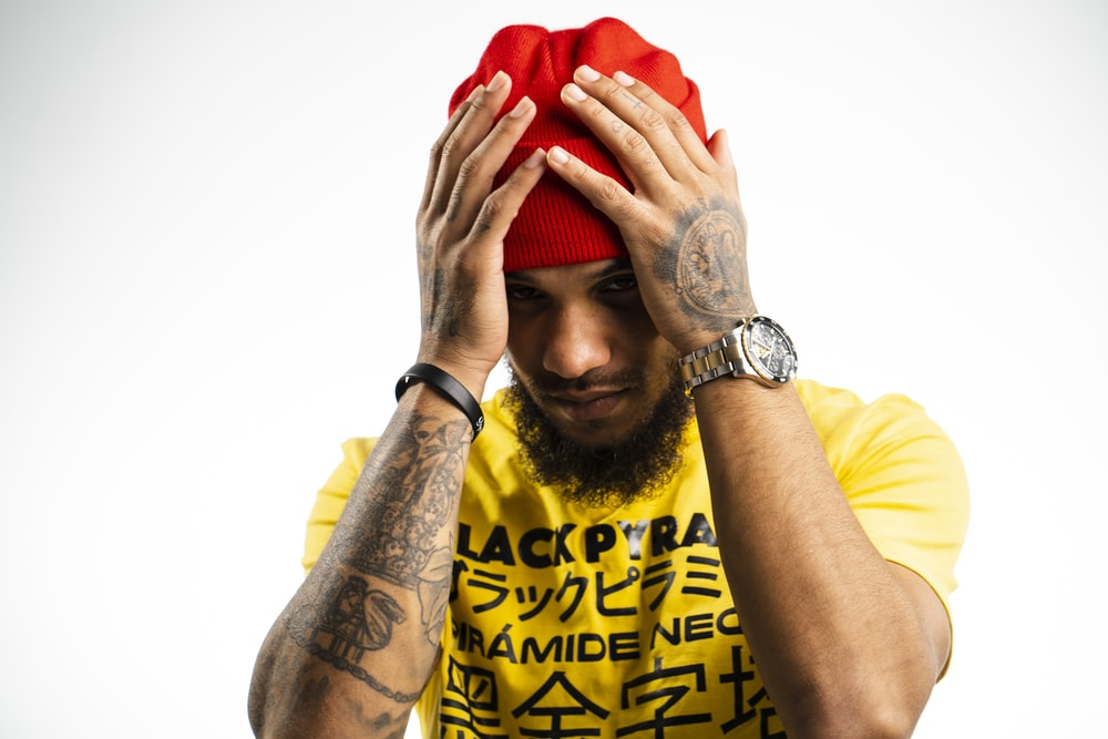 man wearing yellow and black printed crew-neck t-shirt and red knit cap putting both hands on his head