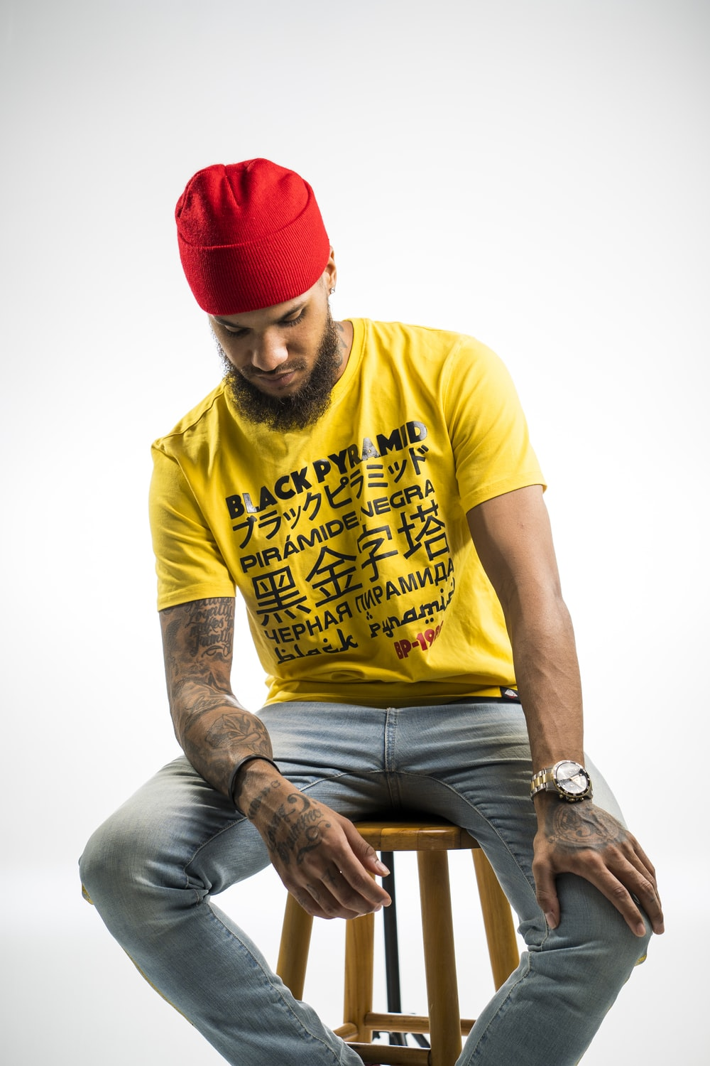 man wearing yellow and black printed crew-neck t-shirt and red knit cap sitting in wooden stool while looking down