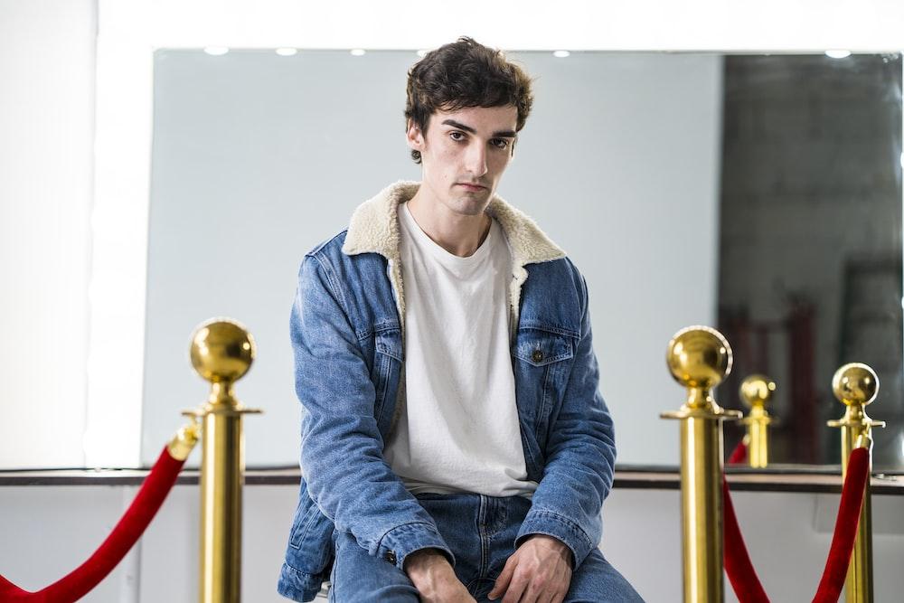 man wearing blue and white denim jacket sitting near brass stanchion
