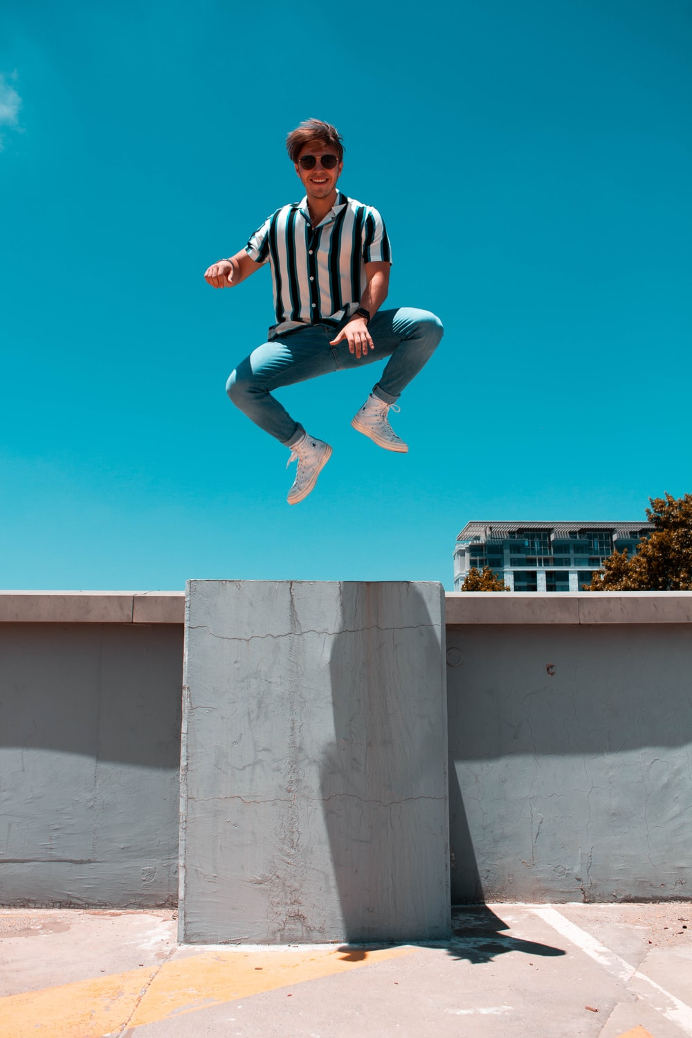 man in mid air above concrete floor and fence during day