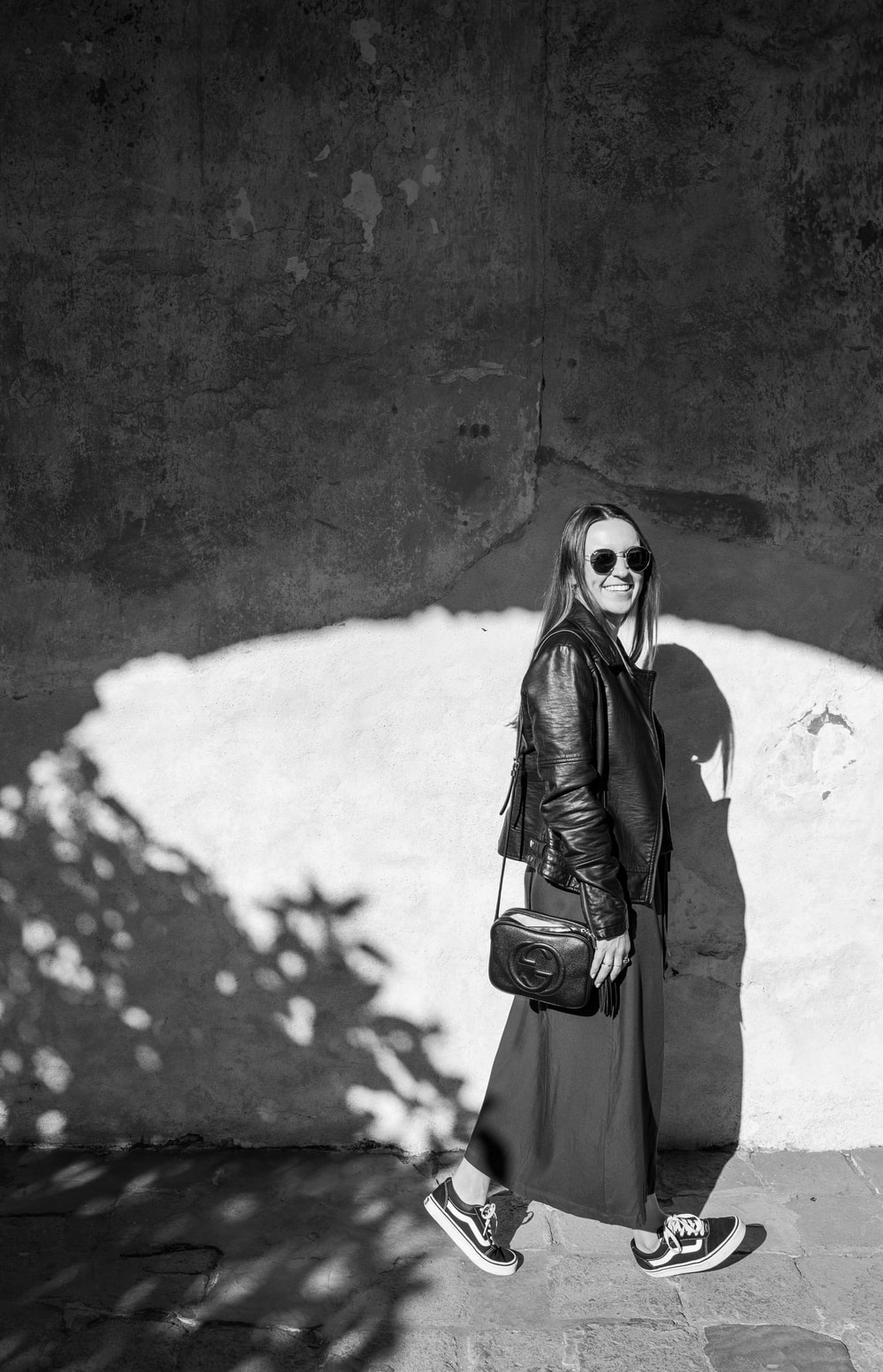 grayscale photography of woman wearing leather zip-up jacket and sunglasses walking on pathway smiling