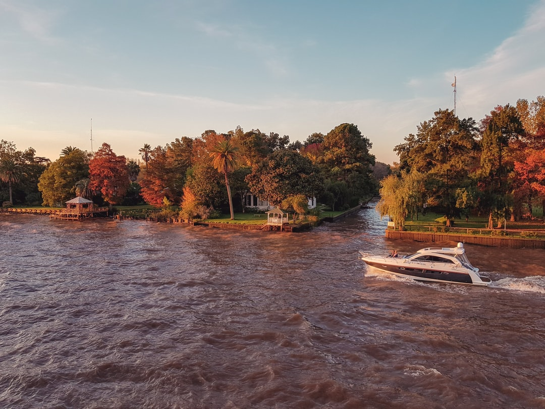 Small yacht sails in a warm spring sunset at the river.
