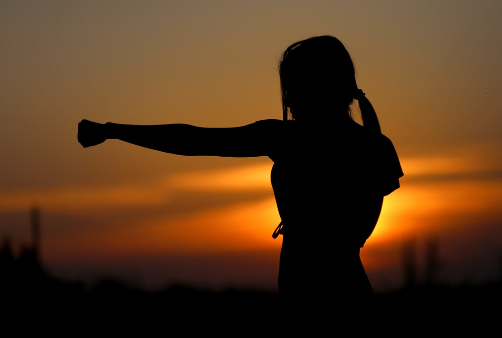 woman punching the air during golden hour