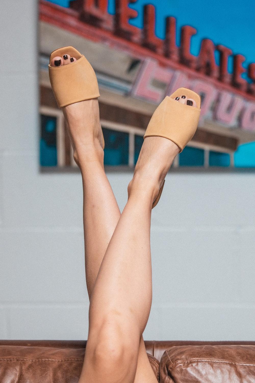 woman raising her legs wearing sandals