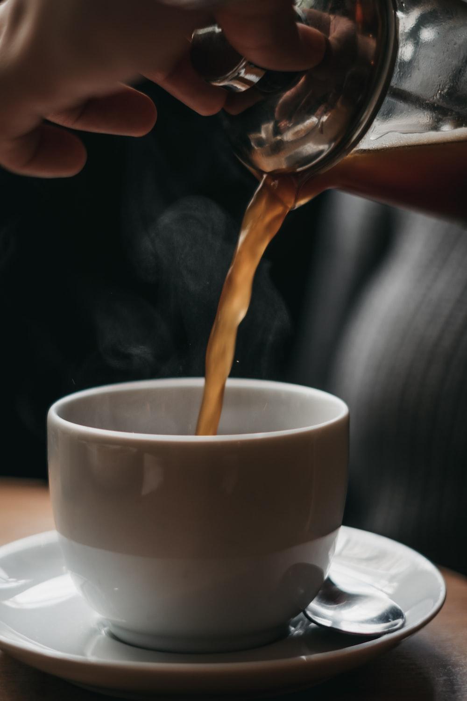 person pouring coffee in white ceramic mug