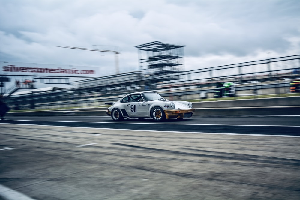 panning photography of white coupe