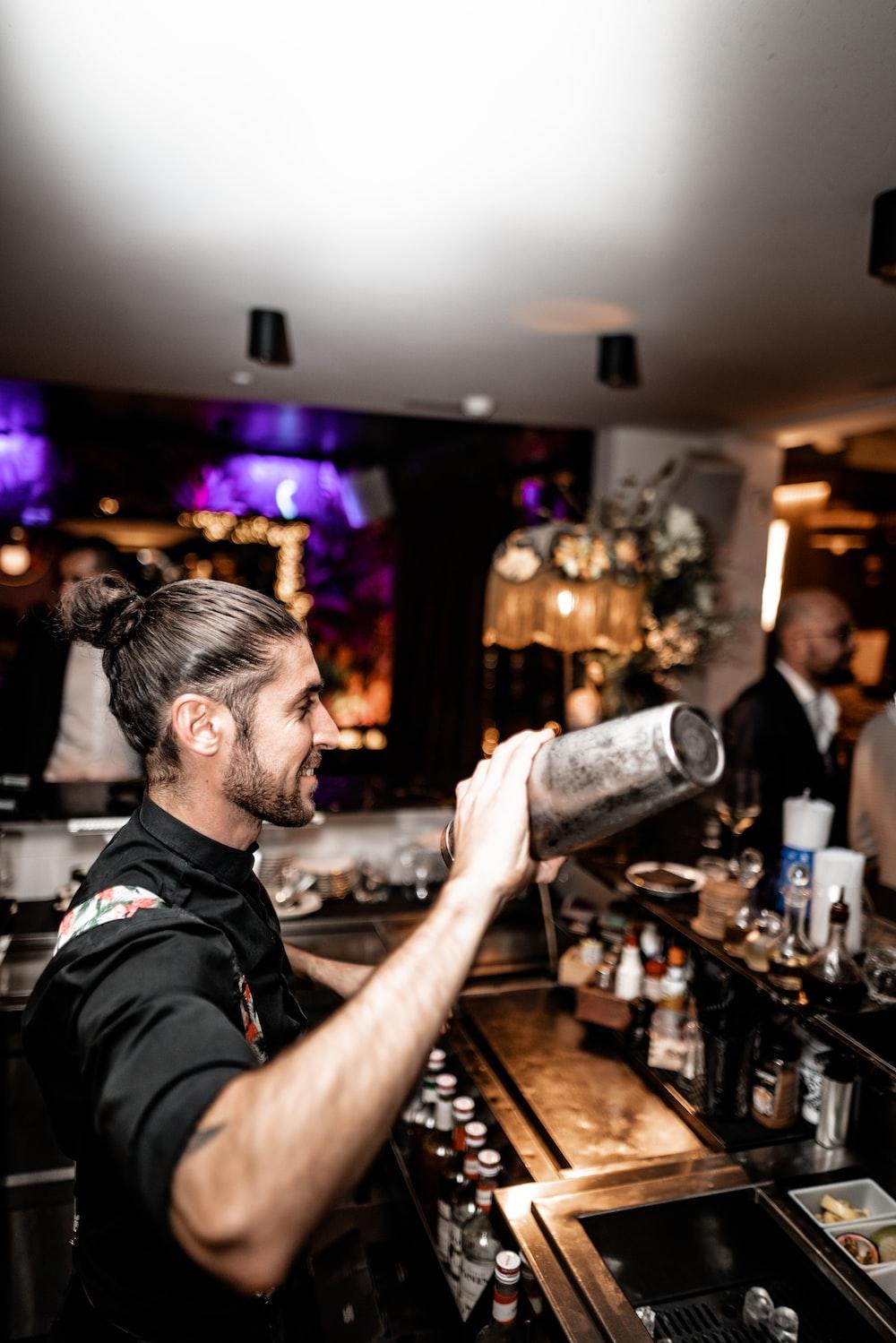 man holding bar shaker inside bar