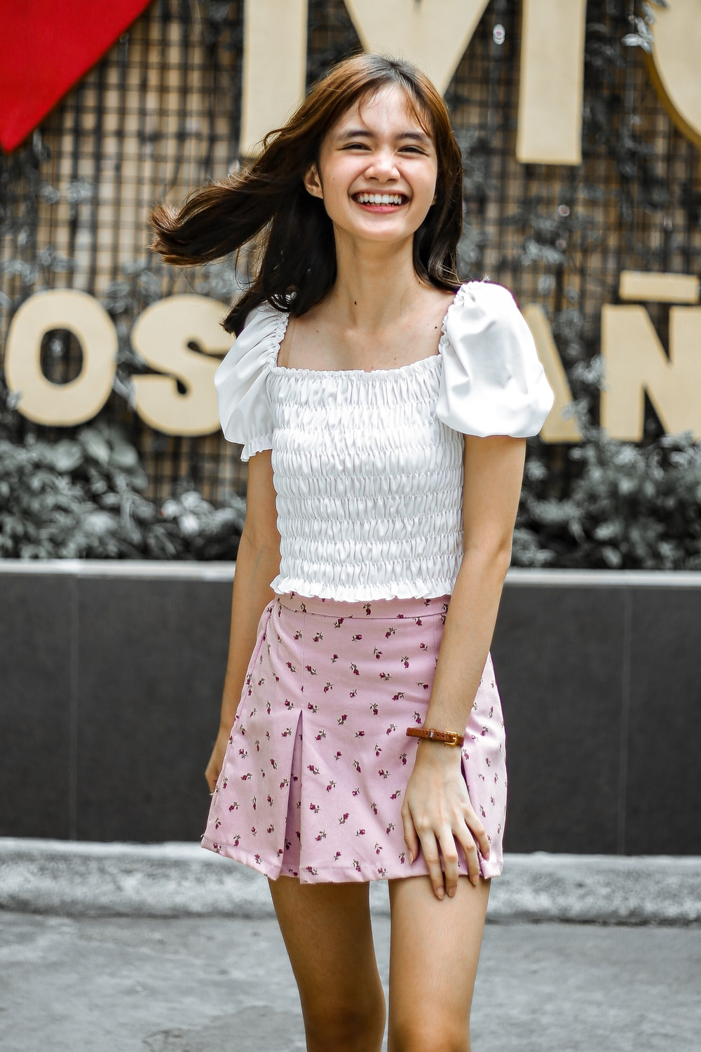 woman in white crop-top and pink skirt