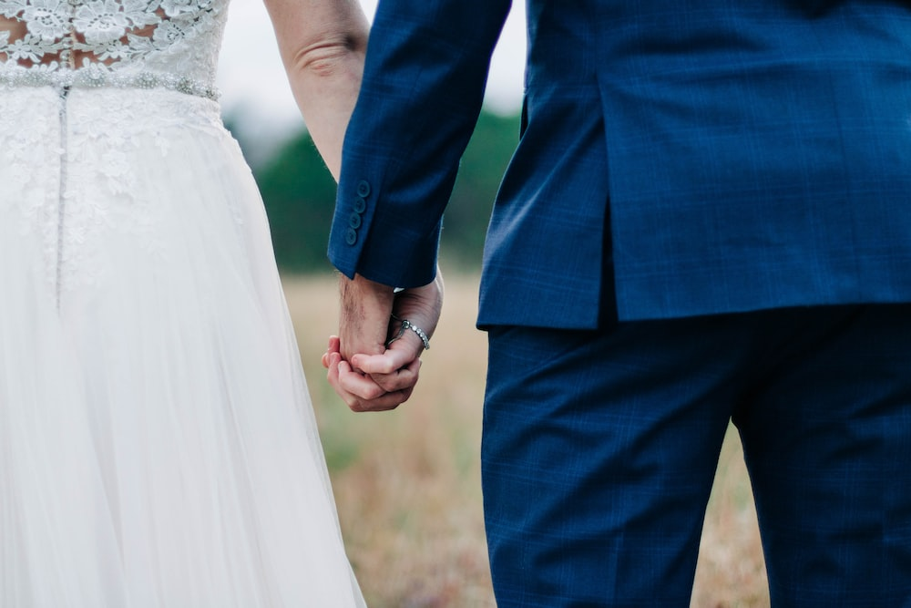 woman wearing white wedding dress and man wearing blue suit holding hands during daytime