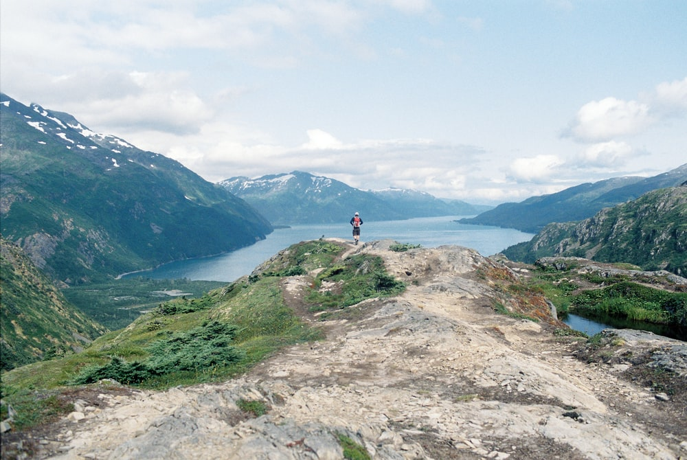 person standing on mountain edge facing the river and mountains during day