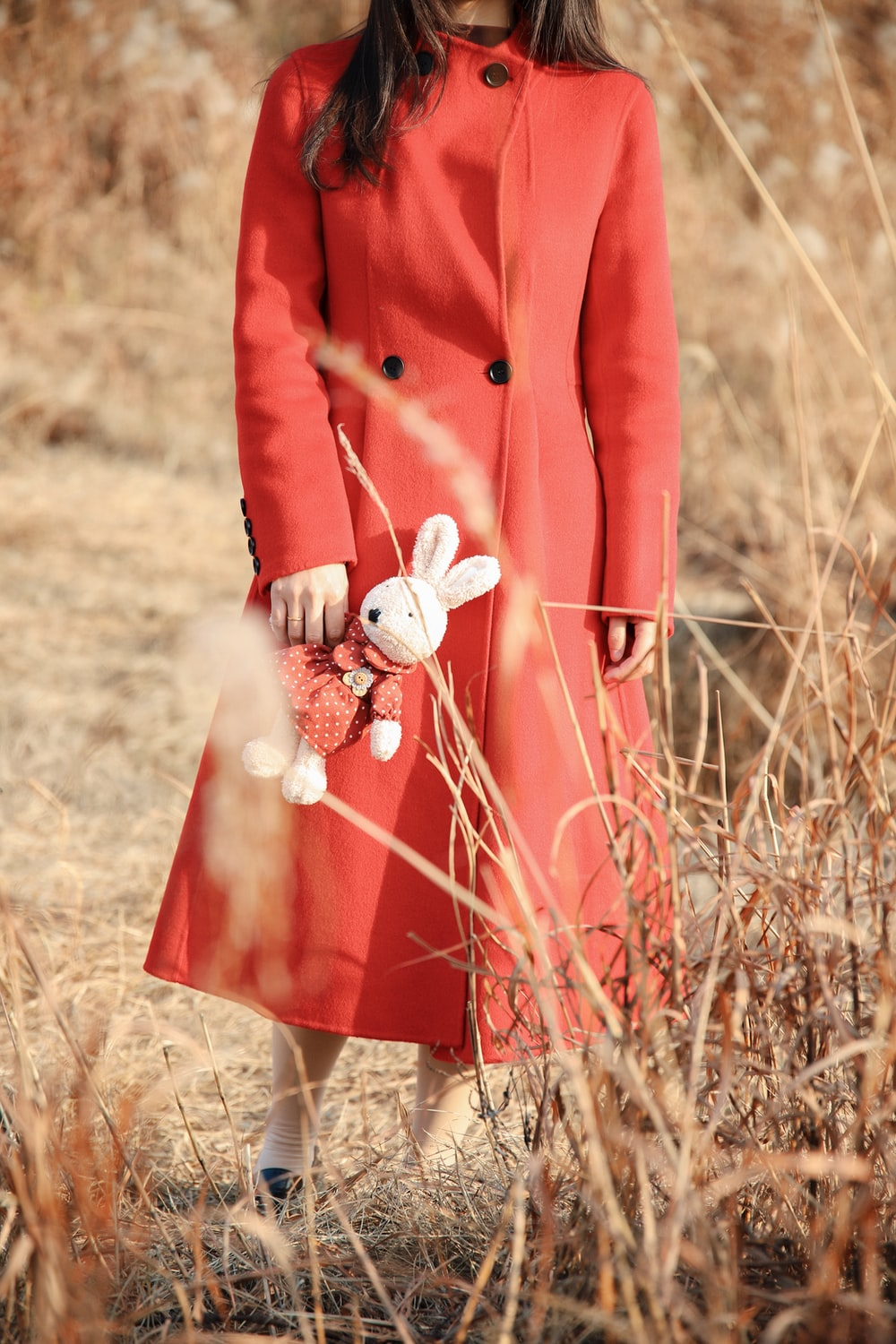 woman in red coat holding bunny plush toy