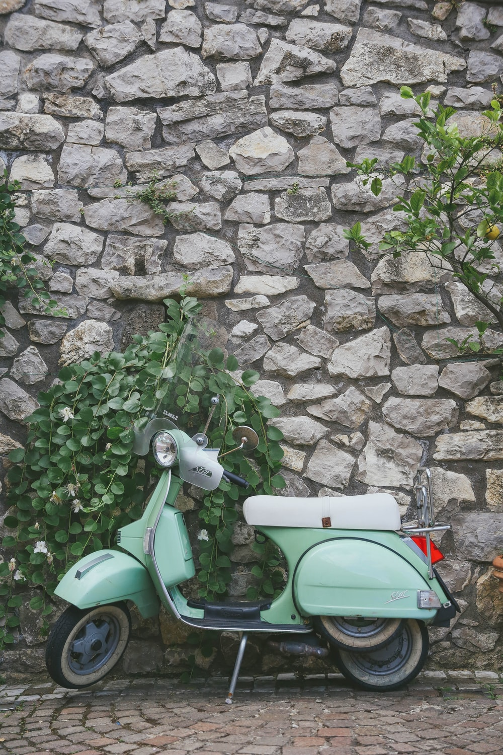 parked green motor scooter beside stone wall
