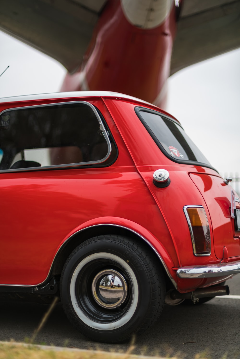 selective focus photography of red hatchback during daytime