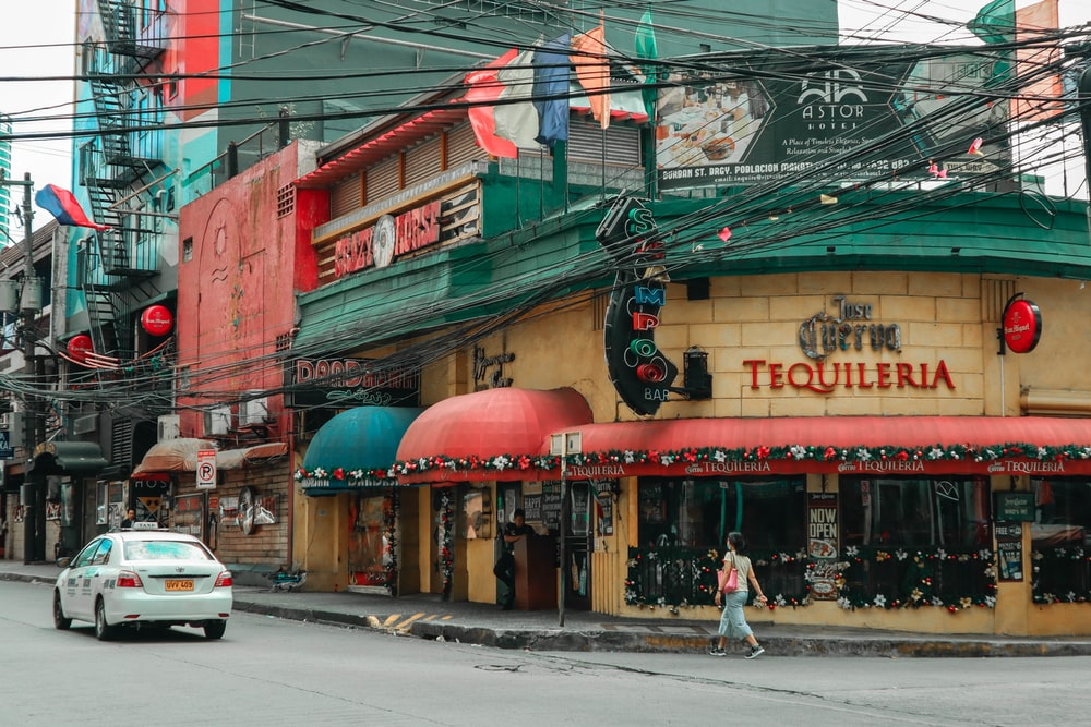 Tequileria building near white sedan on road and woman walking during day