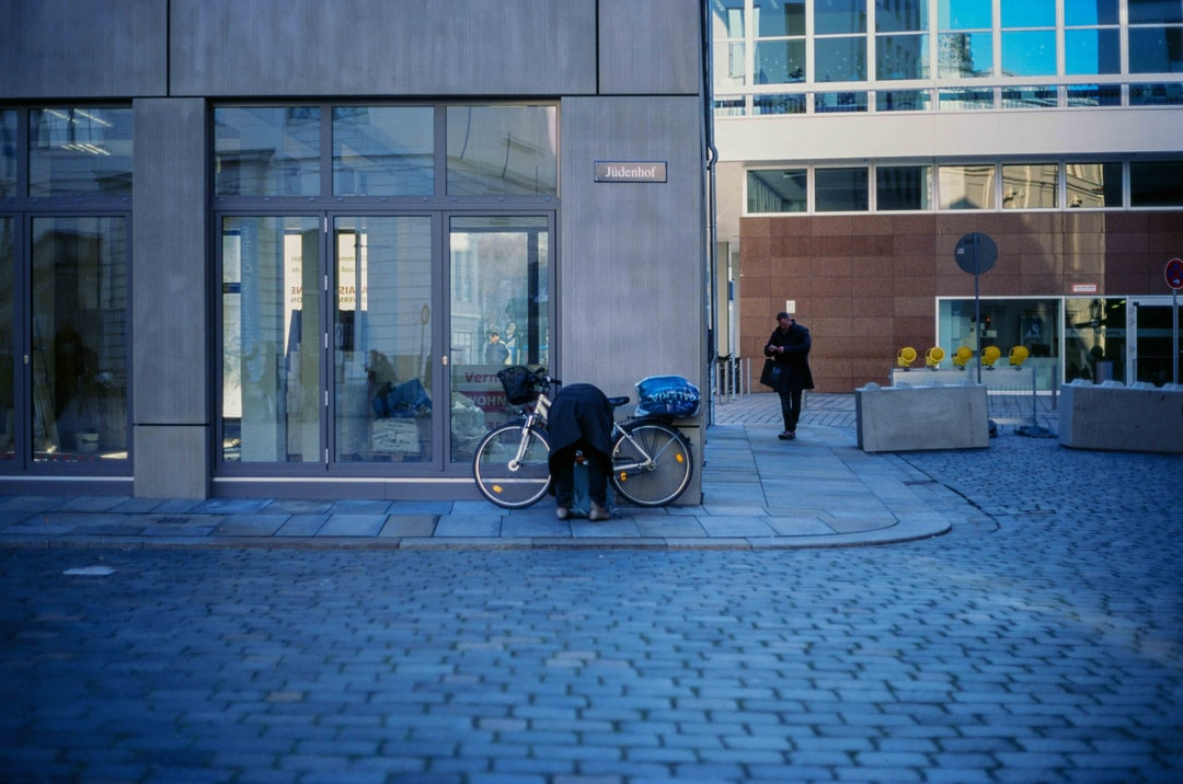 Person Parking Bicycle On Sidewalk - unsplash