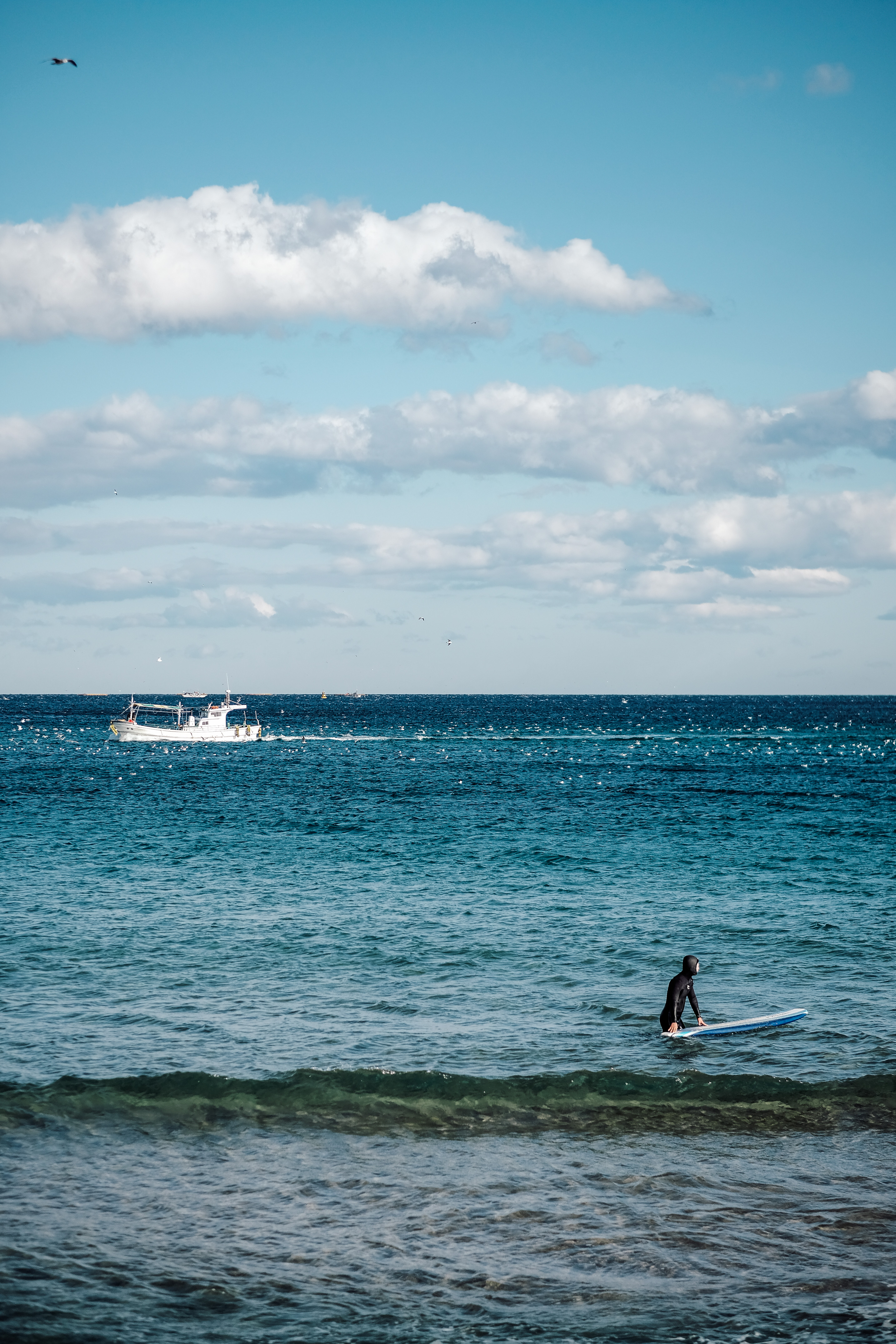 person with surfboard near boat at the ocean during day