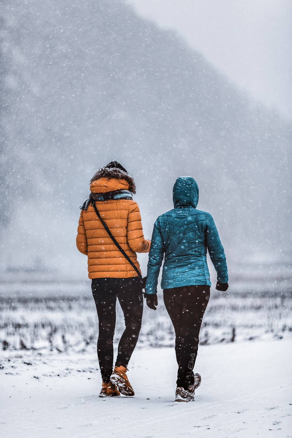 man and woman walking on snow covered ground