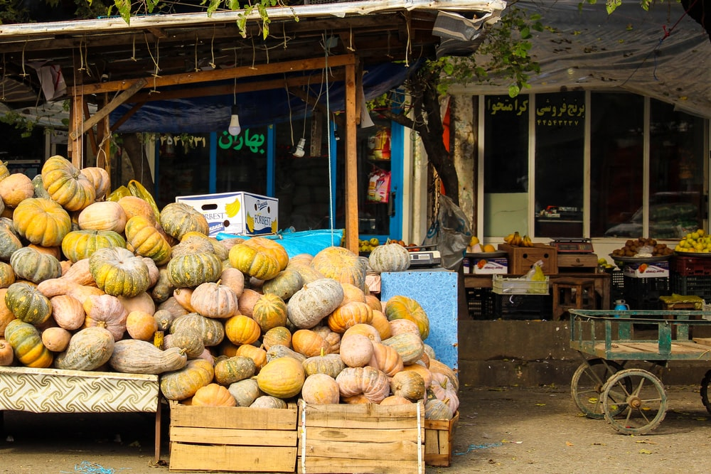 orange and yellow squash in brown wooden crates near store