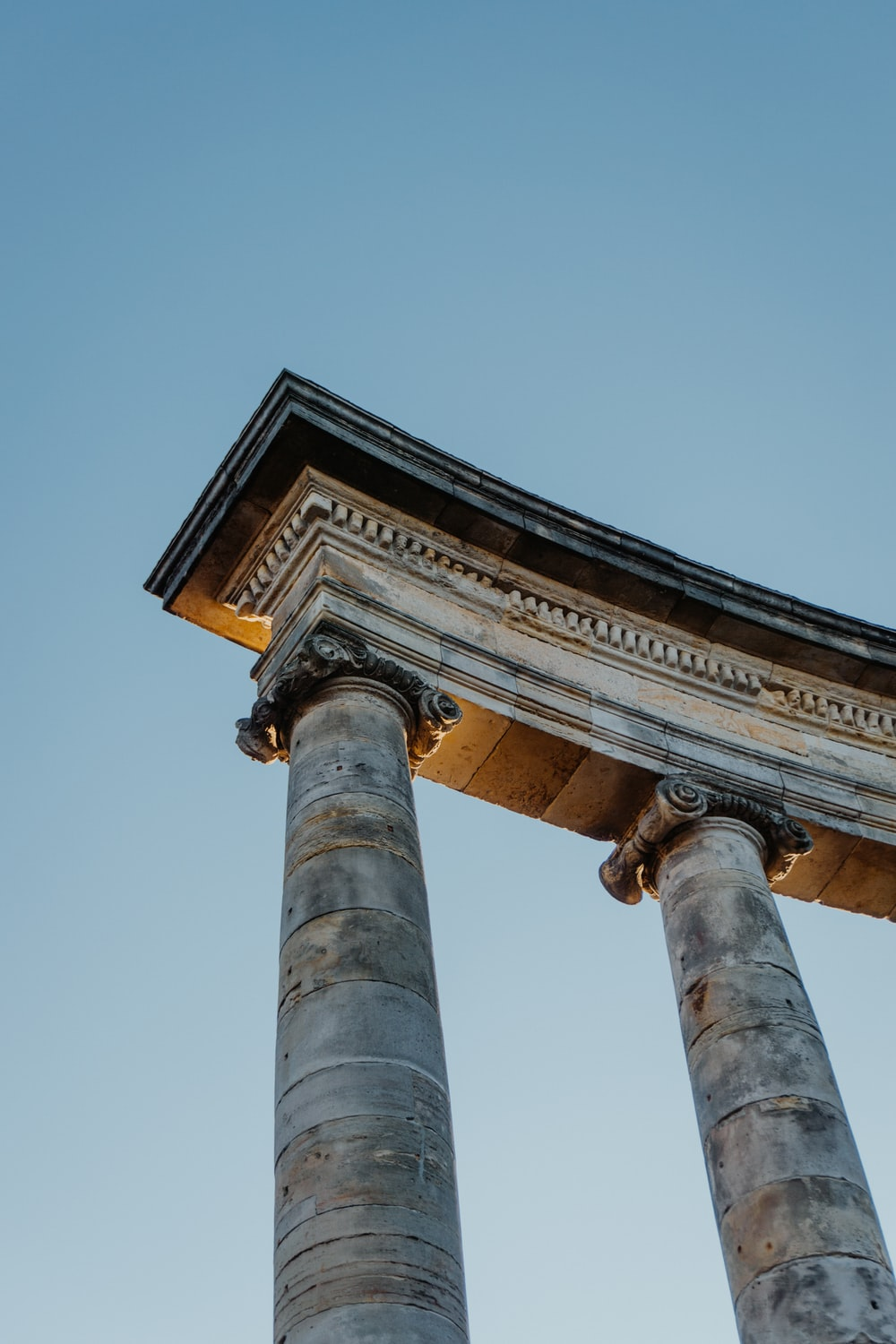 low-angle photography of brown historic column