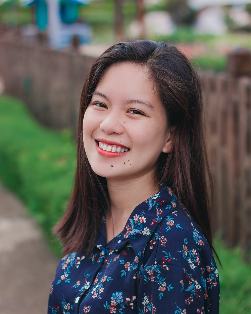 portrait photography of woman wearing blue and red floral collared top smiling