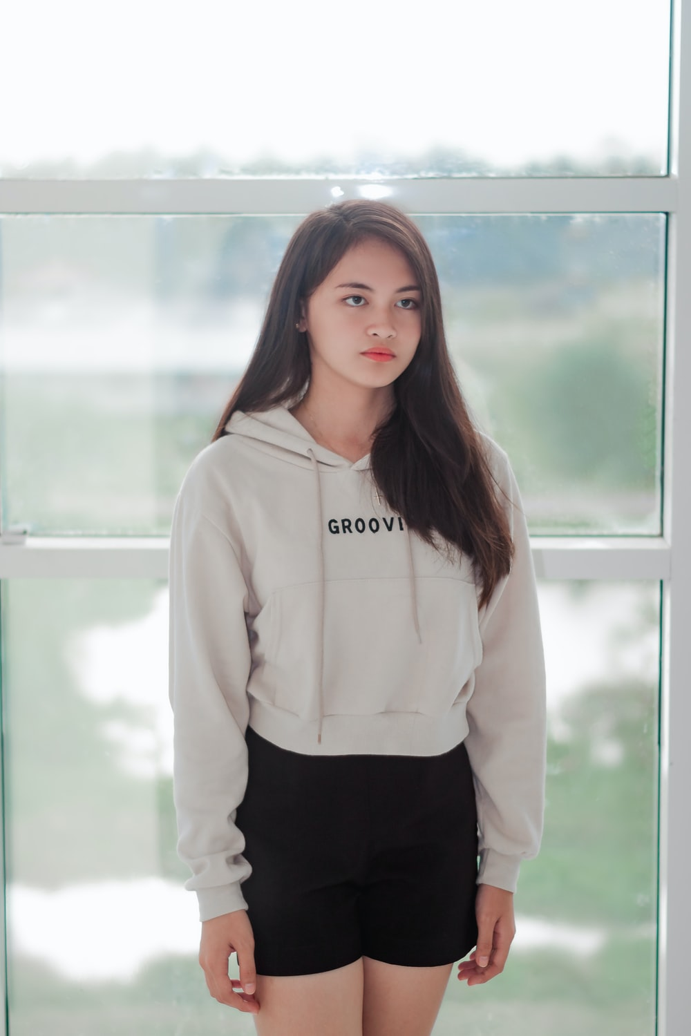 woman wearing white pullover hoodie standing near clear glass wall