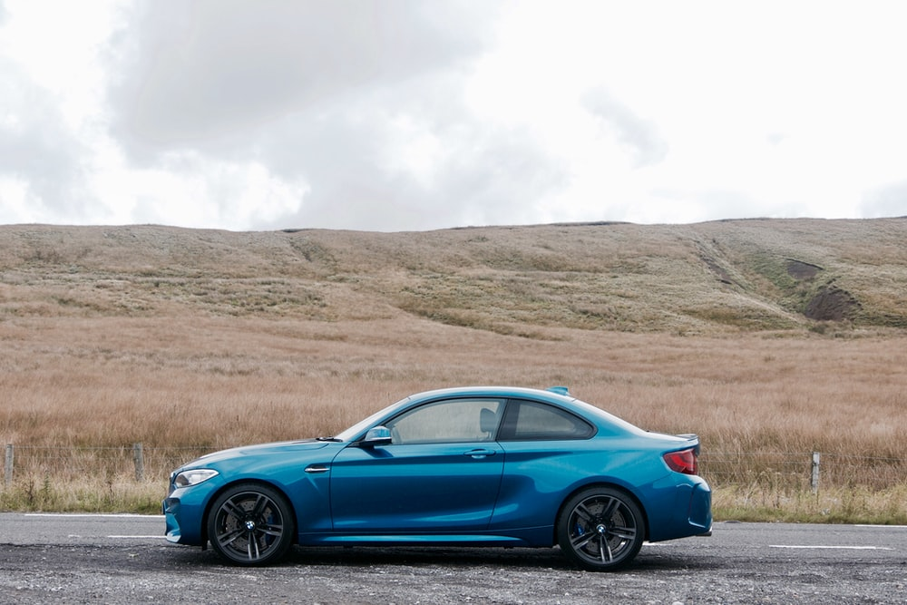 blue BMW coupe on road near empty field at daytime