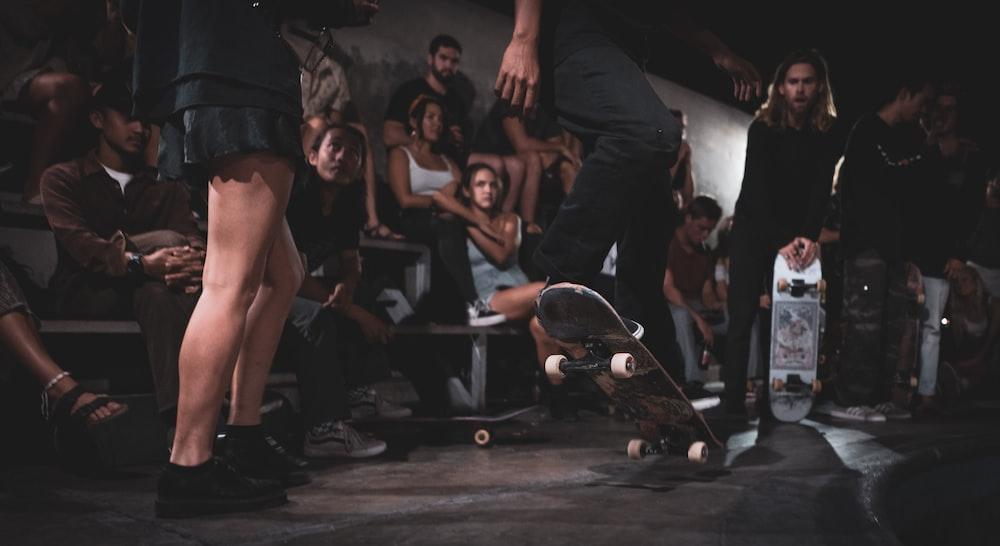 men and women watching person doing skateboard stunt