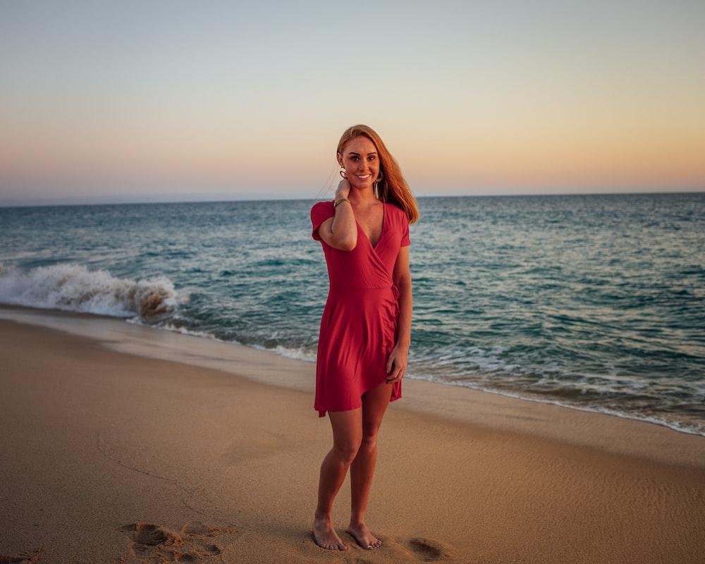 woman in red dress walking beside seashore during daytime