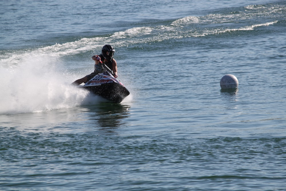shallow focus photo of person riding personal watercraft