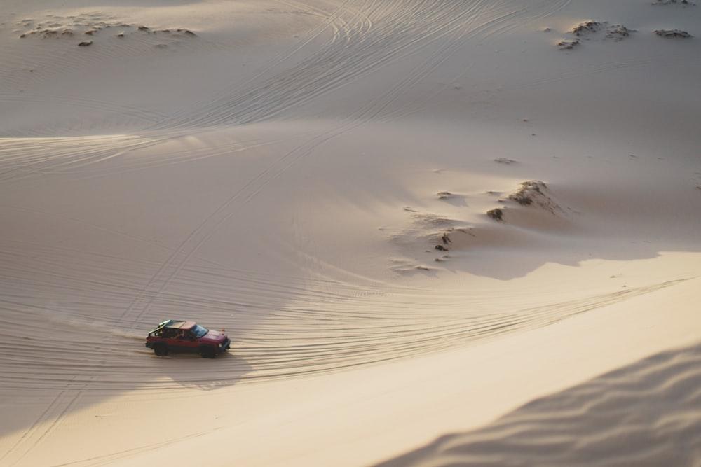 brown car running on desert sand