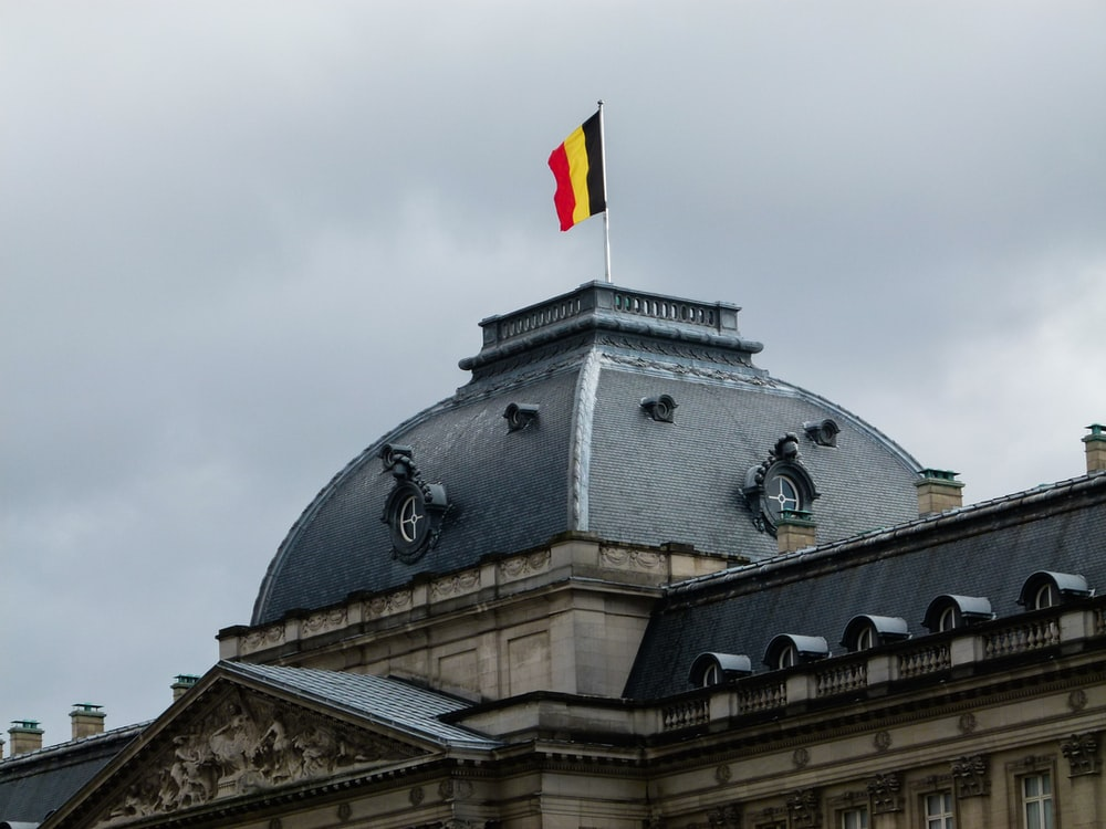 gray and white building with red, yellow, and black striped flag on roof