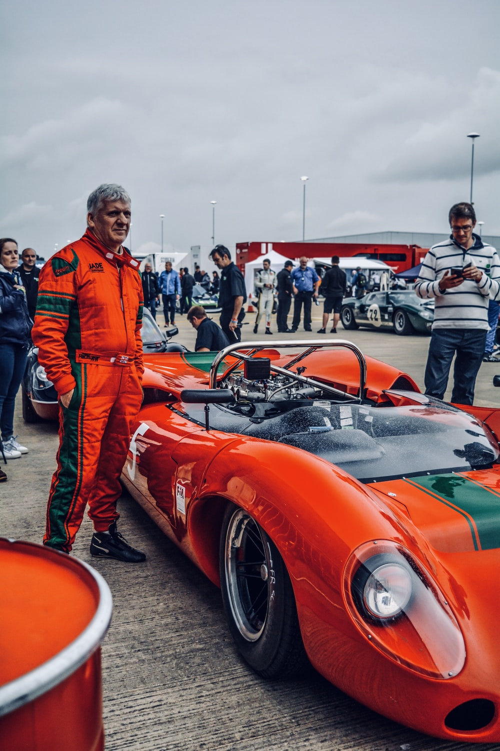 man standing beside red sports car