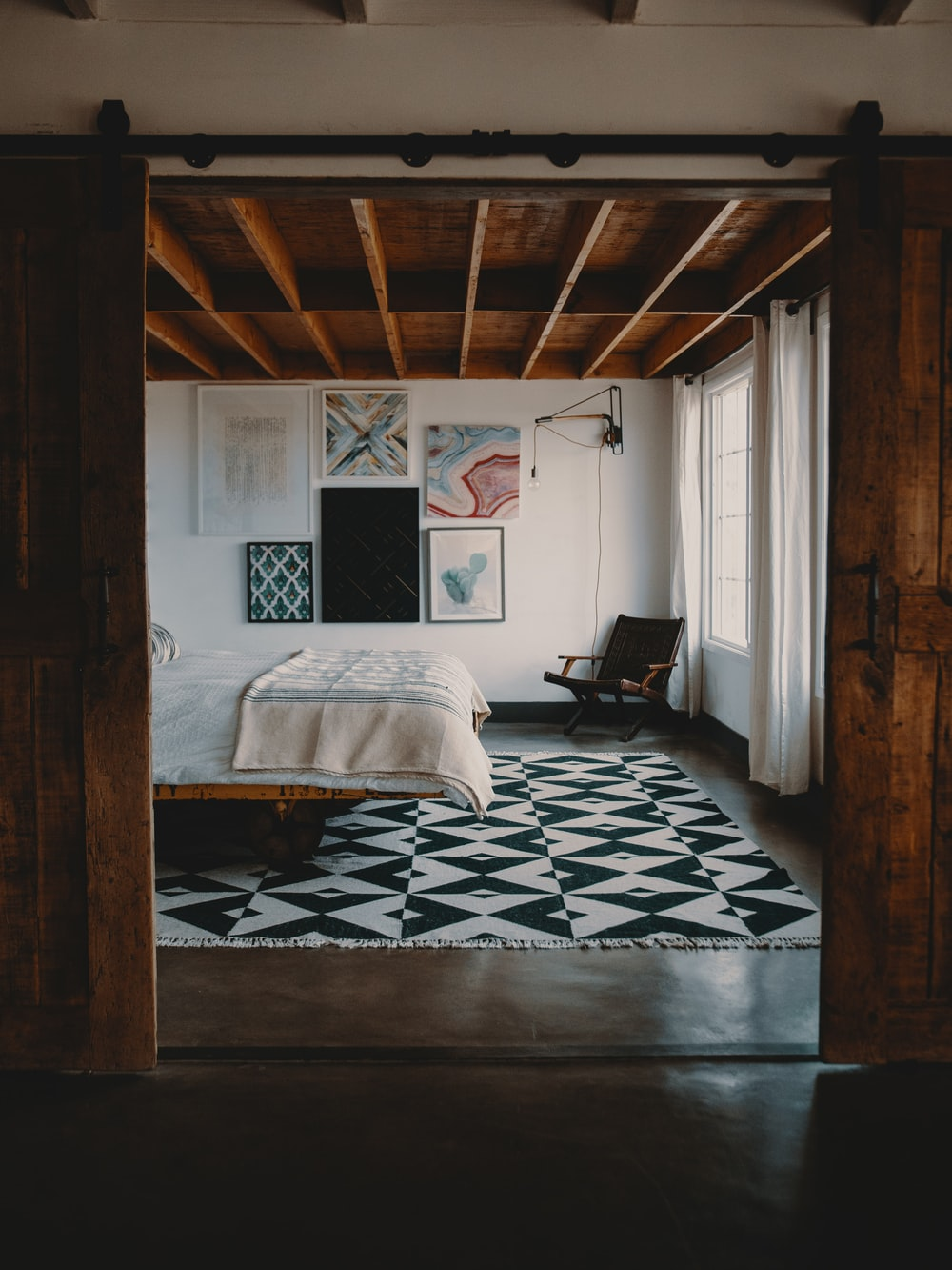 wooden armchair on corner in front of bed