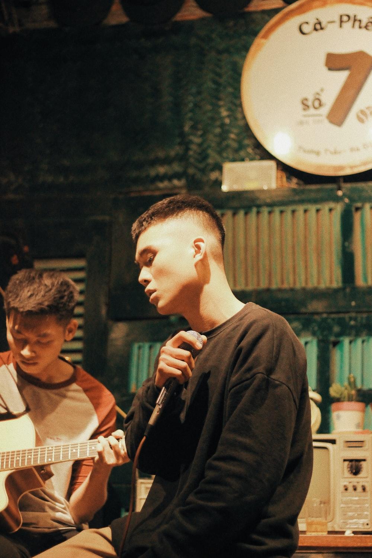 man wearing black crew-neck shirt holding microphone beside man playing guitar