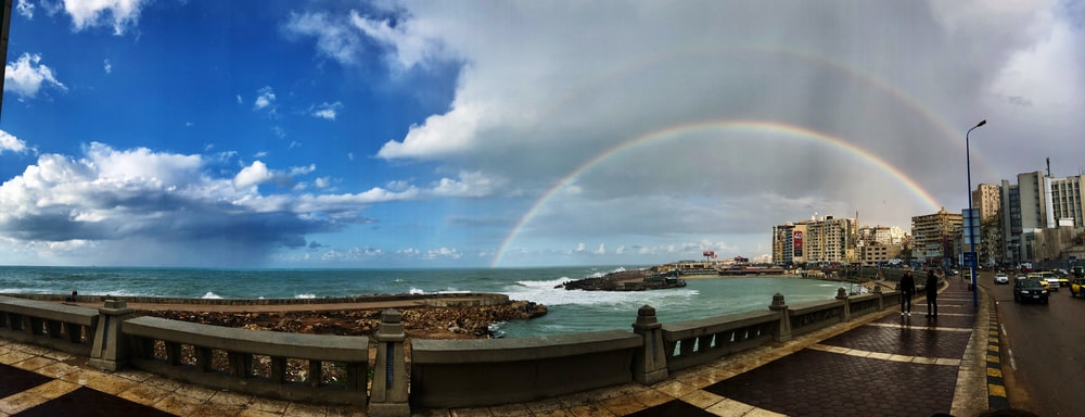 panoramic photography of seawall and rainbow during daytime