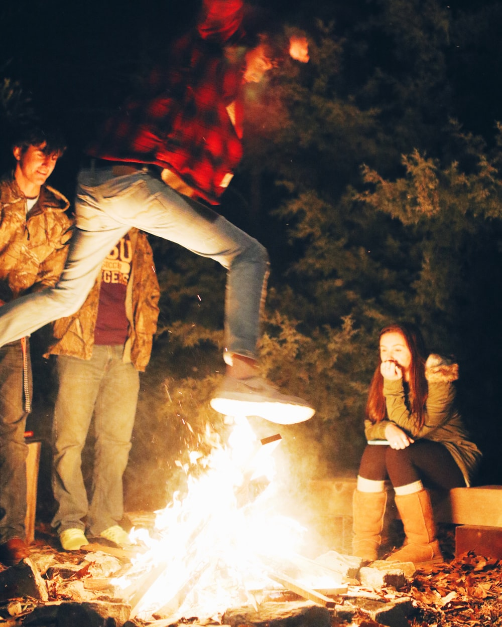 man wearing red and black checked shirt jumping near bonfire