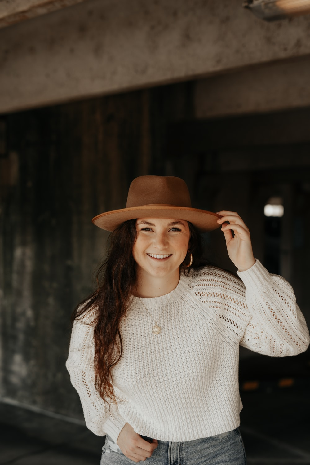 woman smiling and looking at the camera while holding brown hat