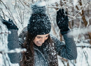smiling woman wearing gray sweater and gloves playing with snow during daytime