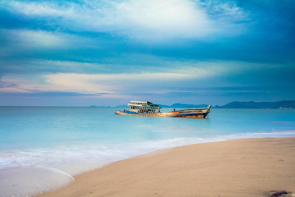 brown boat near seashore