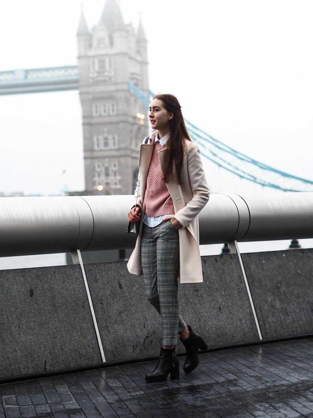 woman in brown overcoat near Tower Bridge