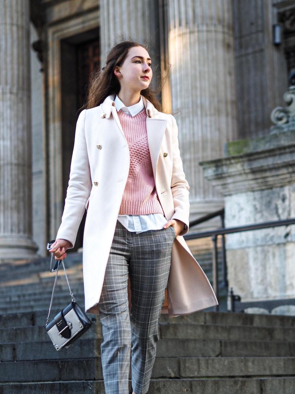 woman wearing white coat carrying crossbody bag