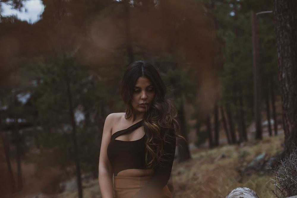 woman wearing black top and brown skirt standing beside trees