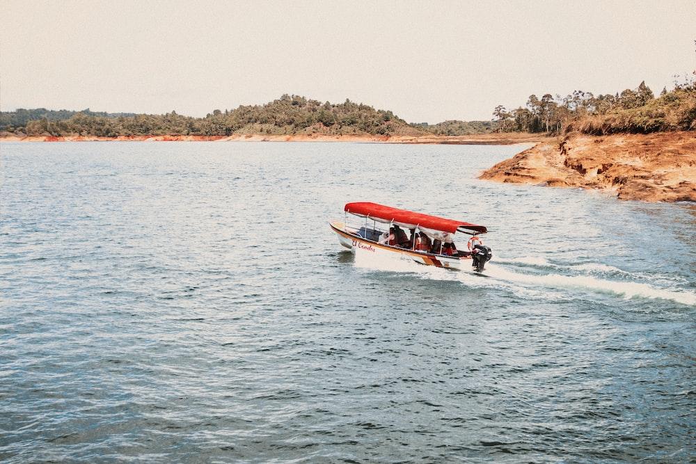 people riding white speedboat during daytime