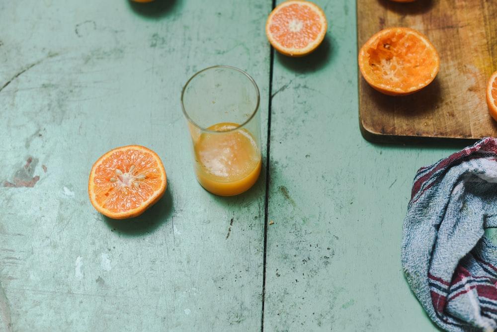 orange juice in glass near sliced orange on wooden chopping board