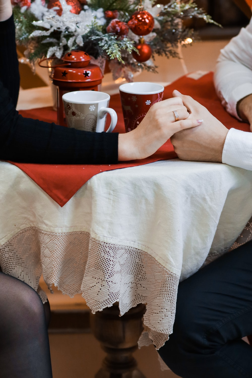 two person sitting near table while holding hands together