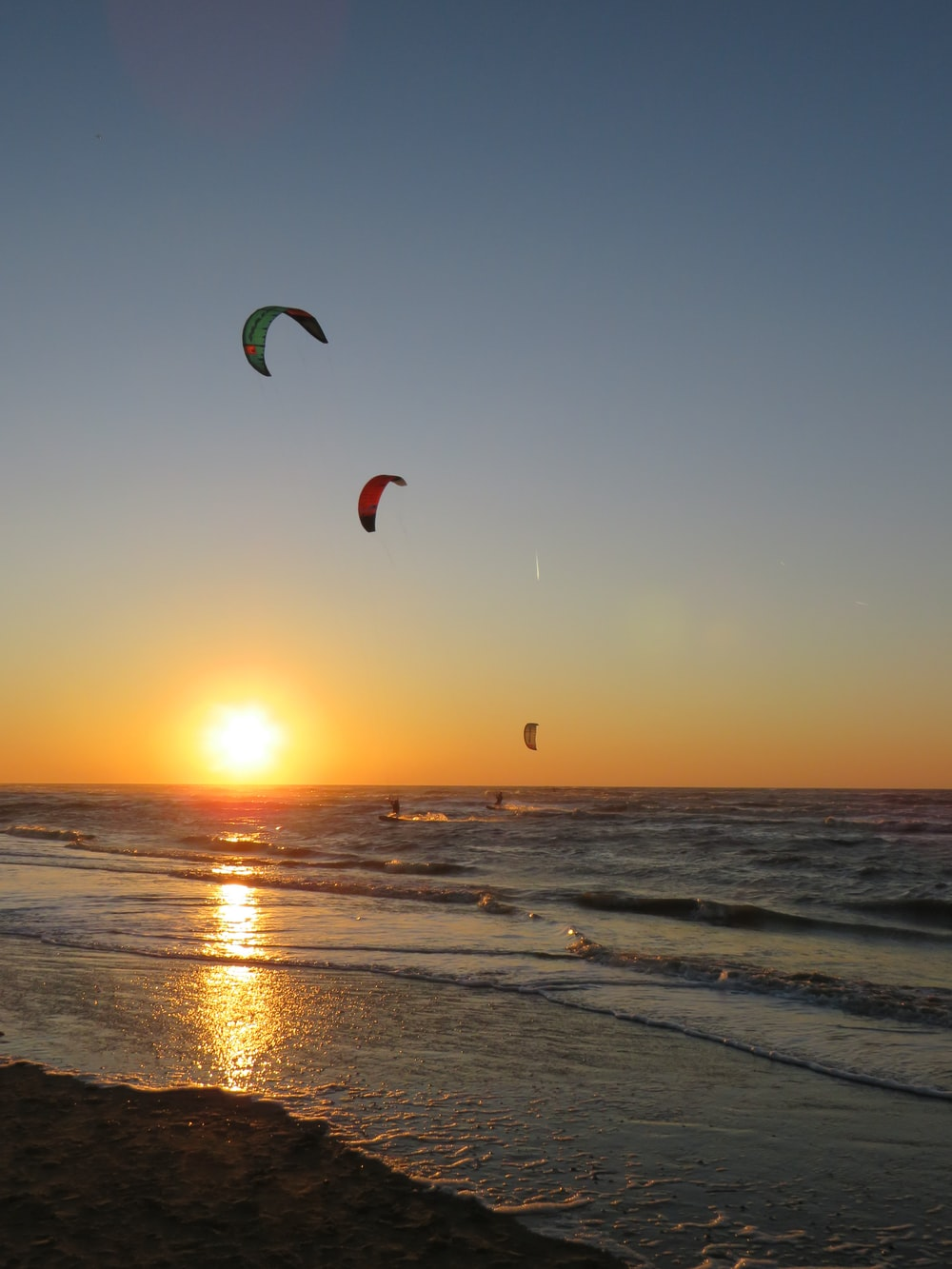 three assorted-color paragliding in seashore during dawn