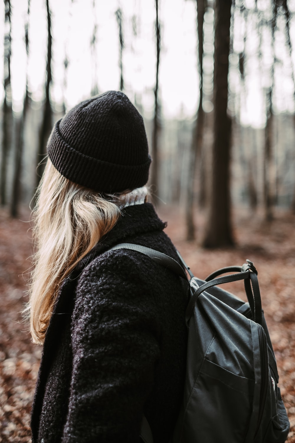 woman wearing black knit cap and jacket with backpack in forest during daytime