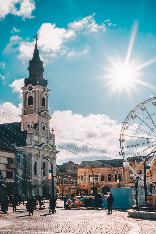 Ferris wheel beside gray concrete church during daytime