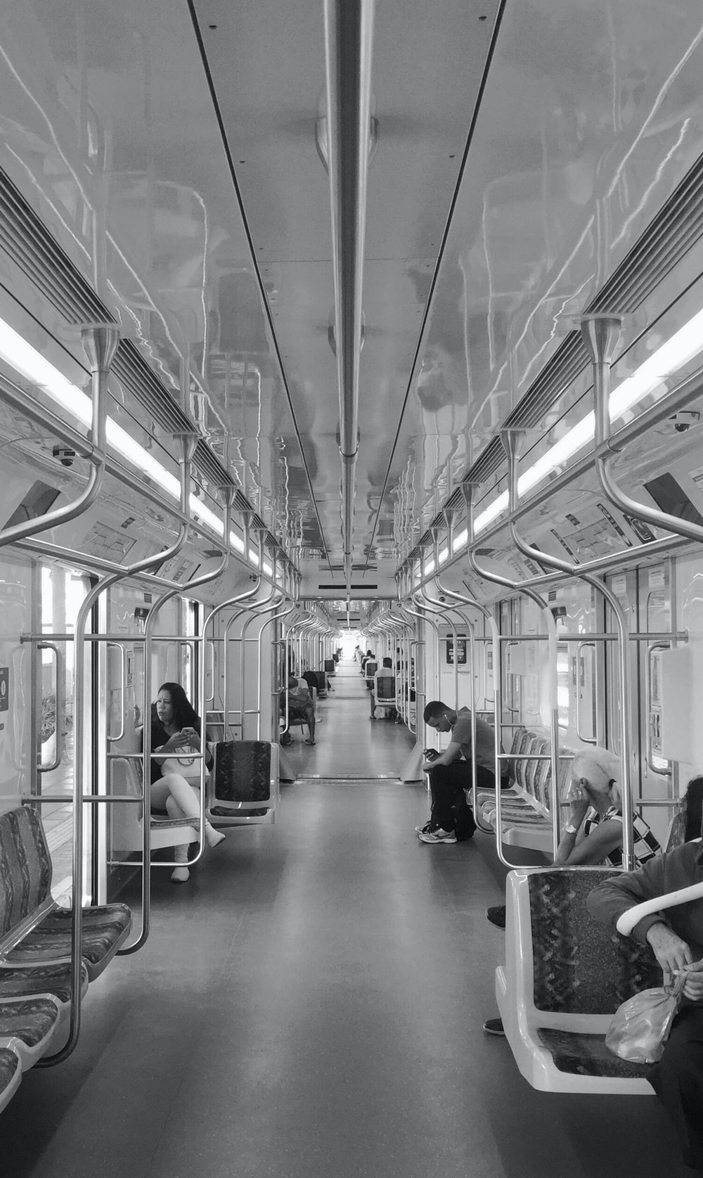 grayscale photography of few people inside train