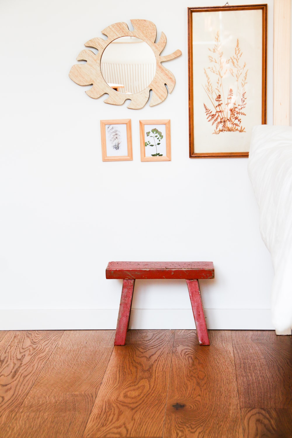 brown wooden bench against white wall